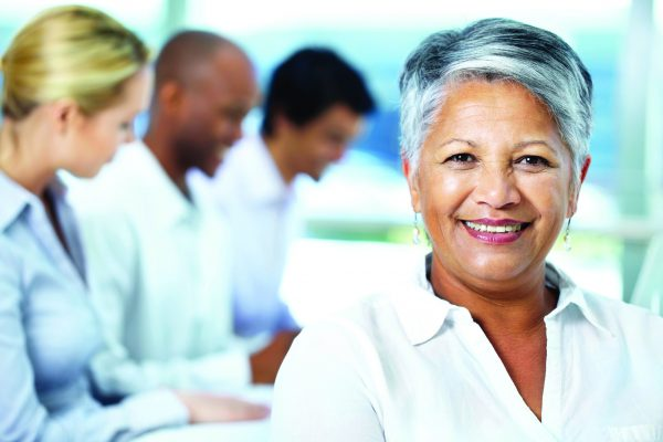Portrait of ethnic businesswoman smiling with coworkers working in the background - copyspace